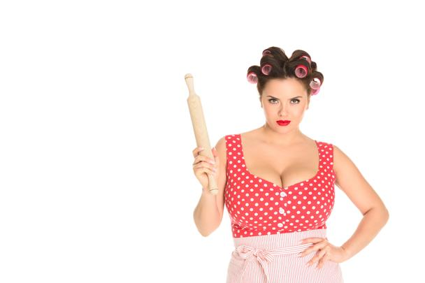 angry plus size housewife with wooden rolling pin looking at camera isolated on white - Photo, Image