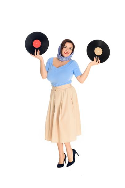 full length view of beautiful size plus pin up woman holding vinyl records and smiling at camera isolated on white  - Photo, Image