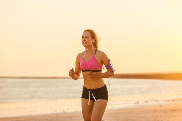female jogger in earphones with smartphone in armband case running on beach with sea behind  - Photo, Image