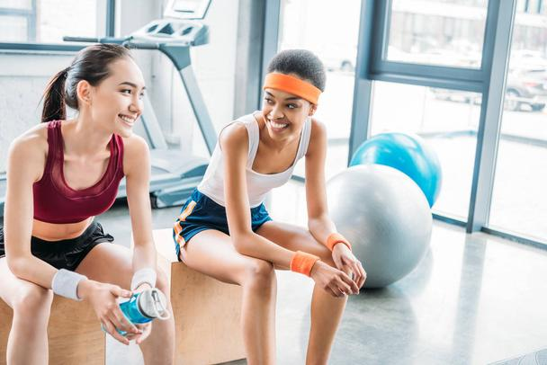 smiling african american sportswoman and asian sportswoman with bottle of water sitting on wooden boxes at gym - Photo, Image