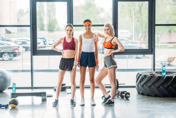 young attractive multiethnic sportswomen posing at gym  - Photo, Image