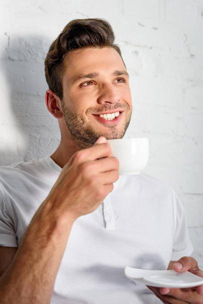 handsome smiling young man drinking coffee at morning at home - Photo, Image