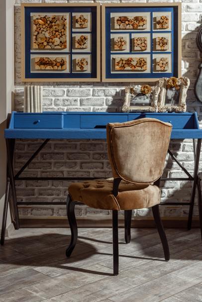 Interieur eines modernen Wohnzimmers im Retro-Stil mit blauem Tisch, Stuhl und Fotos in Rahmen - Foto, Bild