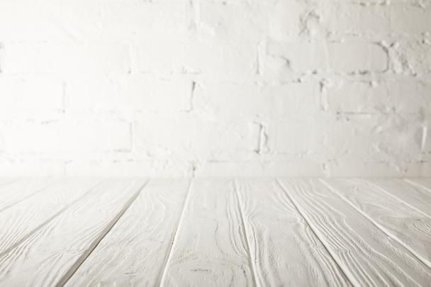 white wooden tabletop and white wall with bricks - Photo, Image