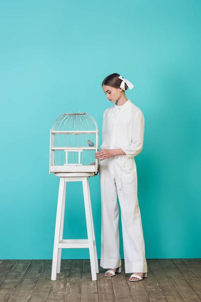 fashionable teen girl in stylish white outfit looking at parrot in cage, on turquoise - Photo, Image