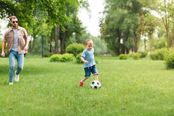 father and son playing football together at park - Photo, Image