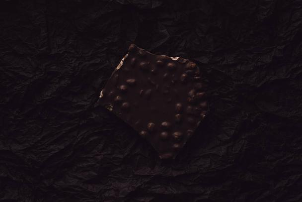 top view of chocolate with pieces of nuts on surface covering by black crumpled paper  - Photo, Image