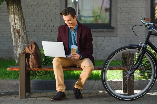 smiling young freelancer holding paper cup and using laptop while sitting on bench - Photo, Image