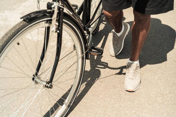 Обрізаний подання афро-американських чоловік, що стоїть на своєму велосипеді - Фото, зображення