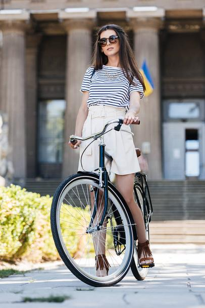 stylish young woman in sunglasses with retro bicycle standing on street - Photo, Image