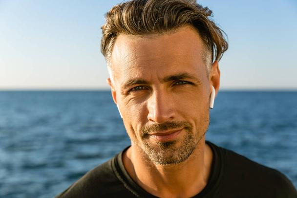 close-up portrait of smiling adult man with wireless earphones on seashore looking at camera - Photo, Image