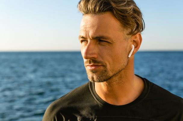 close-up portrait of handsome adult man with wireless earphones on seashore looking away - Photo, Image
