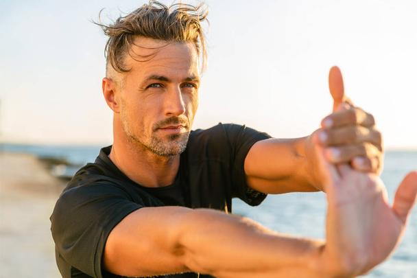 close-up shot of handsome adult sportsman stretching hand before training on seashore - Photo, Image