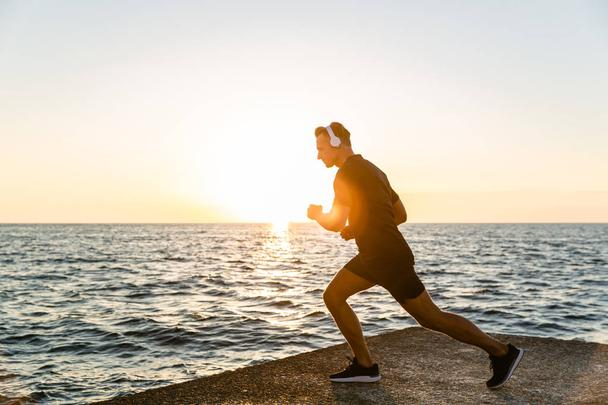sporty adult man in headphones doing one legged squats during training on seashore - Photo, Image