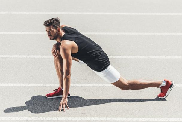 male jogger stretching on running track at sport playground  - Photo, Image