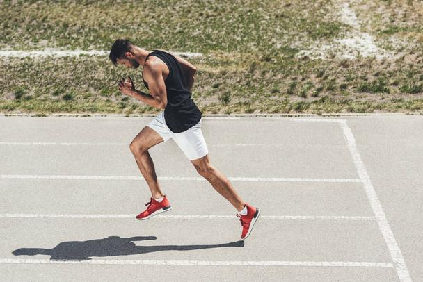 side view of male sprinter running on athletic track at sport playground - Photo, Image