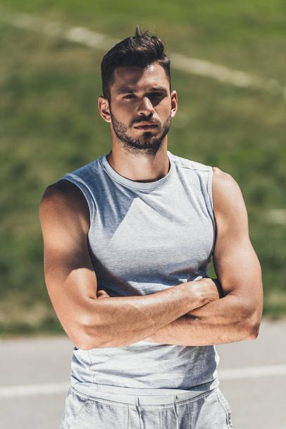 handsome young man in sportswear looking at camera with crossed arms - Photo, Image