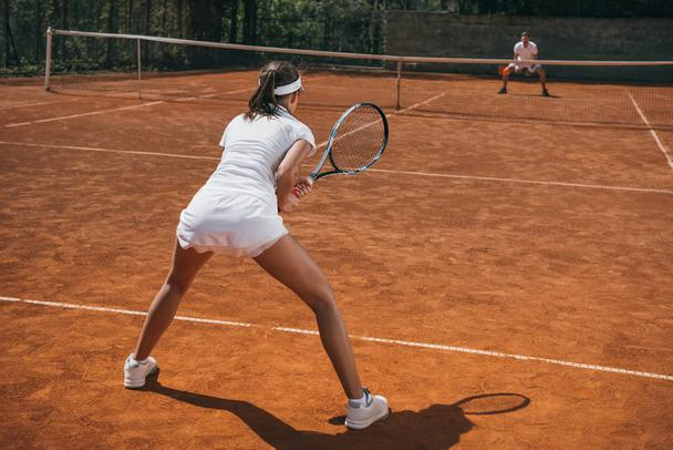 young athlietic woman in sportswear playing tennis with man - Photo, Image