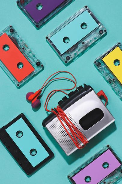 flat lay with colorful retro audio cassettes, cassette player and earphones isolated on blue - Photo, Image