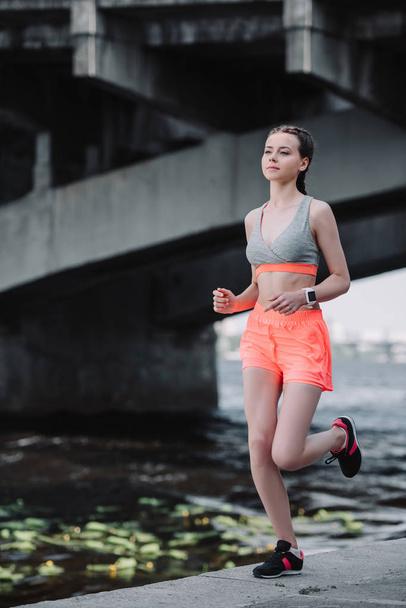 beautiful sportswoman with smartwatch running on quay - Photo, Image