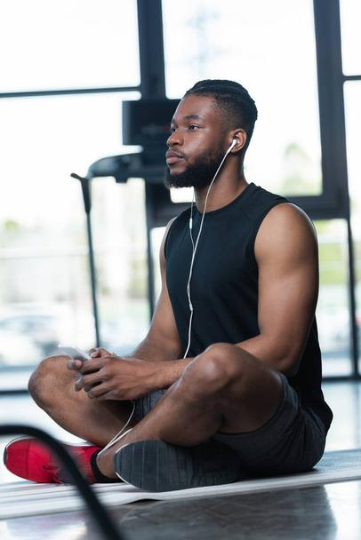 pensive african american sportsman in earphones using smartphone and looking away while sitting on yoga mat in gym - Photo, Image