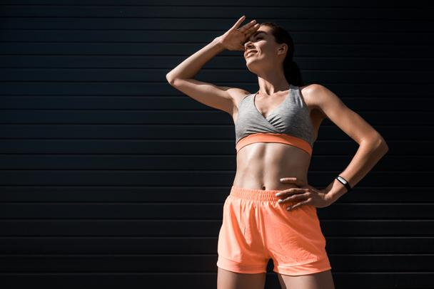 young sportswoman with fitness tracker looking away - Photo, Image