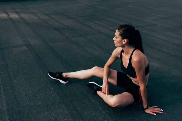 young athletic woman in sportswear sitting on asphalt - Photo, Image
