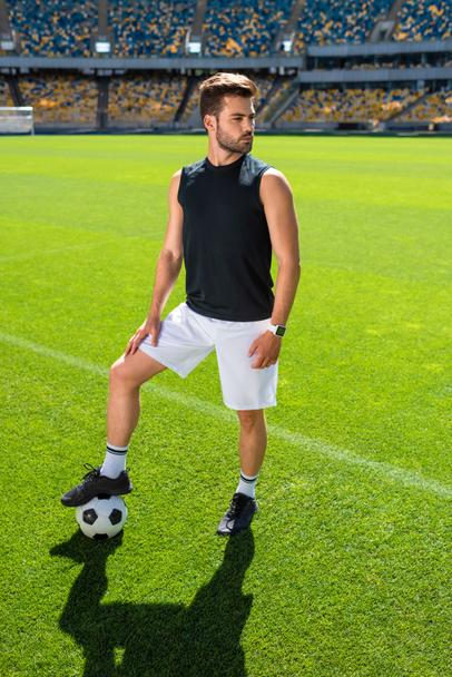 serious young soccer player standing at sports stadium with ball - Photo, Image