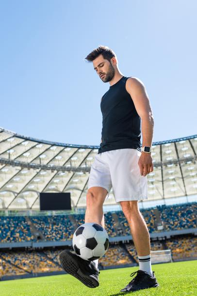 handsome young soccer player exercising with ball at sports stadium - Photo, Image