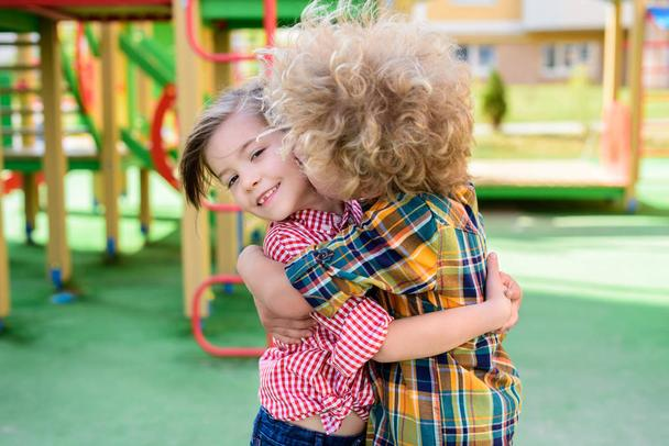selective focus of curly boy kissing and hugging little sister at playground  - Photo, Image