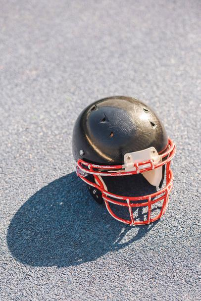 high angle view of american football helmet lying on asphalt - Photo, Image