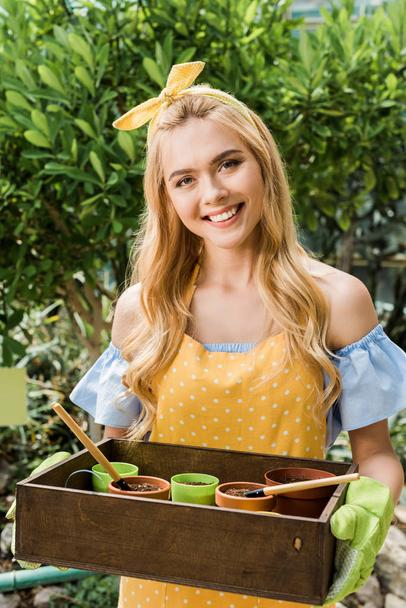 beautiful young female gardener holding box with flower pots and smiling at camera - Photo, Image