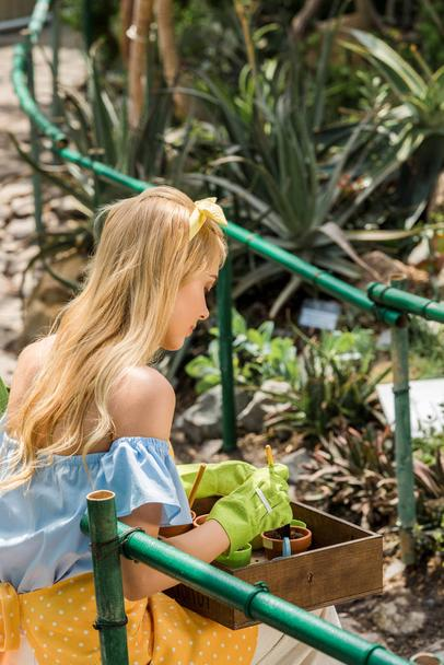 beautiful young woman in rubber gloves growing plants in greenhouse - Photo, Image