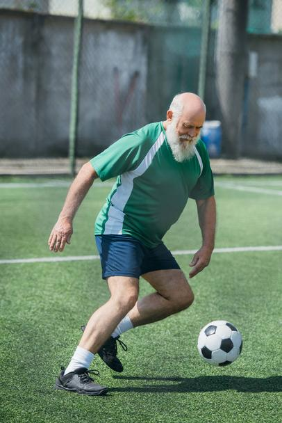 elderly bearded man playing football on field on summer day - Photo, Image