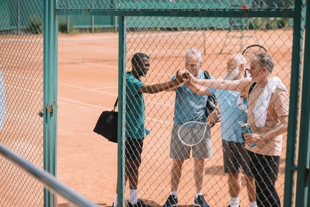 multicultural group of elderly tennis players holding hands together after game on court - Photo, Image