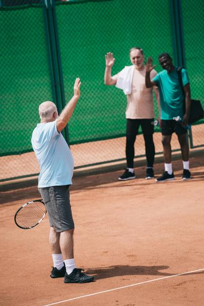 multiethnic old men greeting friend with tennis racquet on court - Photo, Image