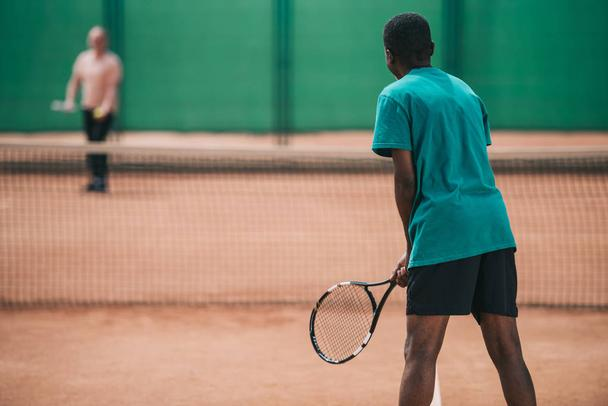 selective focus of elderly african american man playing tennis with friend on court - Photo, Image