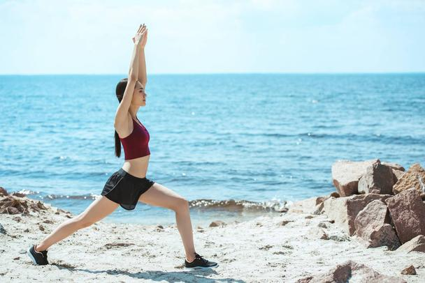 young asian sportswoman exercising on beach in front of sea  - Photo, Image