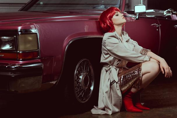beautiful stylish young woman with closed eyes crouching near vintage car   - Photo, Image