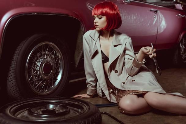 beautiful young woman in trench coat holding wrench and repairing car - Photo, Image