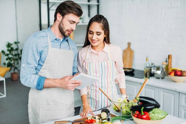 пара, дивлячись на планшет з рецепт під час приготування їжі на кухні - Фото, зображення