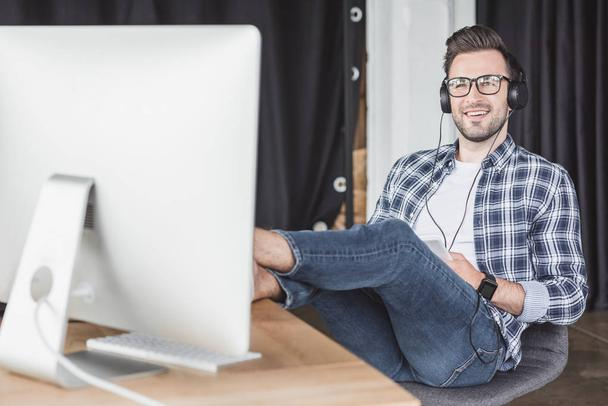 smiling young man in headphones and eyeglasses looking at desktop computer - Photo, Image