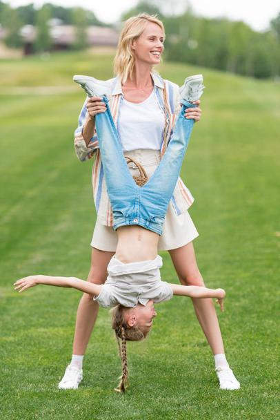 happy mother and little daughter having fun together in park  - Photo, Image