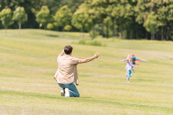 back view of father with open arms looking at little daughter playing with kite in park - Photo, Image