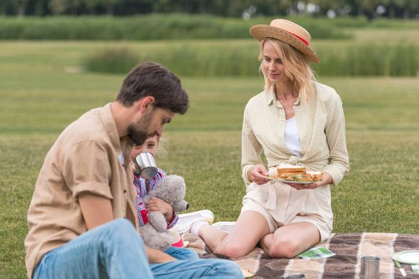 happy family with one child eating sandwiches while sitting on plaid at picnic - Photo, Image