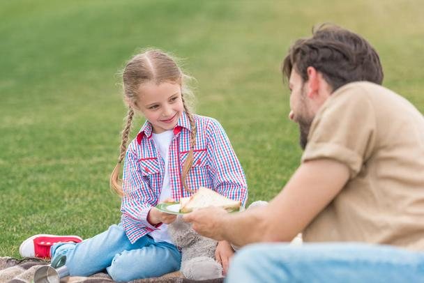 happy father and daughter eating sandwiches at picnic in park - Photo, Image