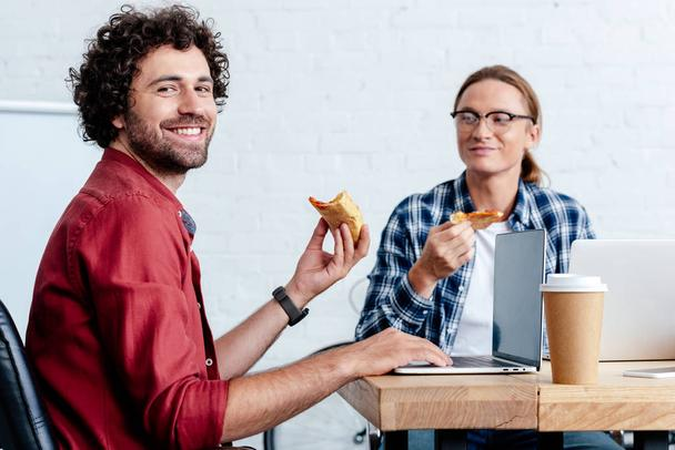 smiling young men eating pizza and using laptops in office - Photo, Image