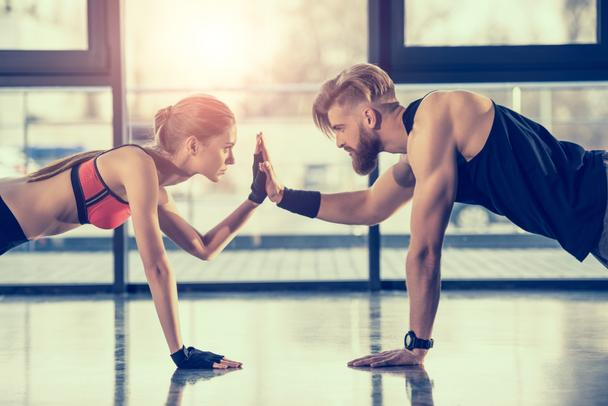 side view of young sportsman and woman doing plank exercise and giving high five - Photo, Image