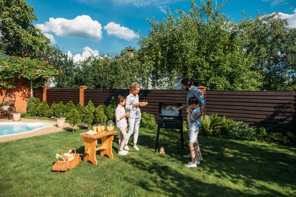 family having barbecue together on backyard on summer day - Photo, Image