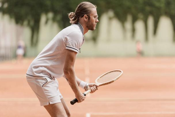 side view of handsome tennis player ready for game with racket at tennis court - Photo, Image